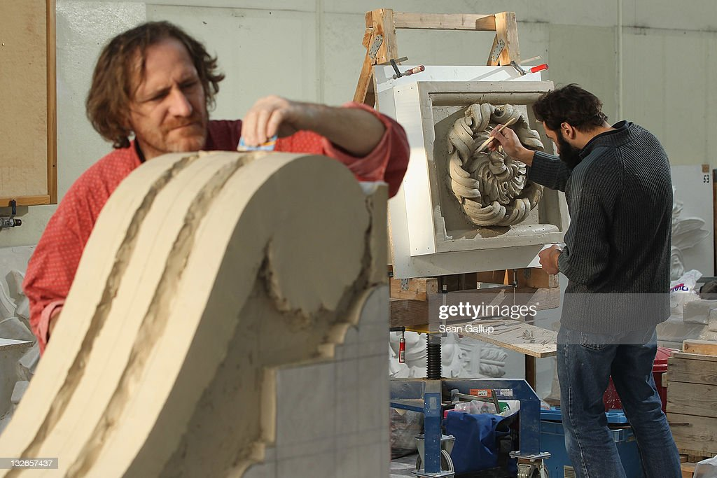 Sculptor Jens Cacha (L) creates a corbel out of clay as his colleague Oleg Bessonov sculpts a rosette at the Schlossbauhuette studio where a team of sculptors is creating decorative elements for the facade of the Berliner Schloss city palace on November 11, 2011 in Berlin, Germany. The Berliner Schloss was the residence of the Prussian Kaiser and was among the major architectural landmarks of Berlin until it was heavily damaged by Allied bombing in 1945. The communist authorities of East Berlin demolished the building in the 1950s, and today's Berlin government is pursuing an ambitious project to rebuild the palace according to a design by Italian architect Franco Stella, which will recreate the facade of the building but with a modern interior at a cost of approximately EUR 590 million. The Humboldt Forum, the foundation leading the project, has given the Schlossbauhuette sculptors the formidable task of recreating the hundreds of architectural elements that decorated the facade, and though some original pieces were saved, more often the sculptors have only old black and white photos as reference.