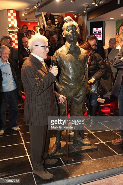 Sculptor Nat Neujean speaks beside his sculpture of the comic hero Tintin during its inauguration at The Comics Village on October 21 2011 in...