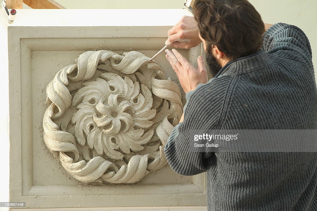 Sculptor Oleg Bessonov creates a rosette from clay at the Schlossbauhuette studio where a team of sculptors is creating decorative elements for the facade of the Berliner Schloss city palace on November 11, 2011 in Berlin, Germany. The Berliner Schloss was the residence of the Prussian Kaiser and was among the major architectural landmarks of Berlin until it was heavily damaged by Allied bombing in 1945. The communist authorities of East Berlin demolished the building in the 1950s, and today's Berlin government is pursuing an ambitious project to rebuild the palace according to a design by Italian architect Franco Stella, which will recreate the facade of the building but with a modern interior at a cost of approximately EUR 590 million. The Humboldt Forum, the foundation leading the project, has given the Schlossbauhuette sculptors the formidable task of recreating the hundreds of architectural elements that decorated the facade, and though some original pieces were saved, more often the sculptors have only old black and white photos as reference.
