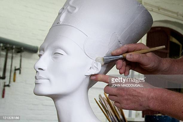 CROP Sculptor Wolfgang Zuehlke cleans a replica of the bust of Nefertiti after removing it from its mould at the Replica Workshop of the National...