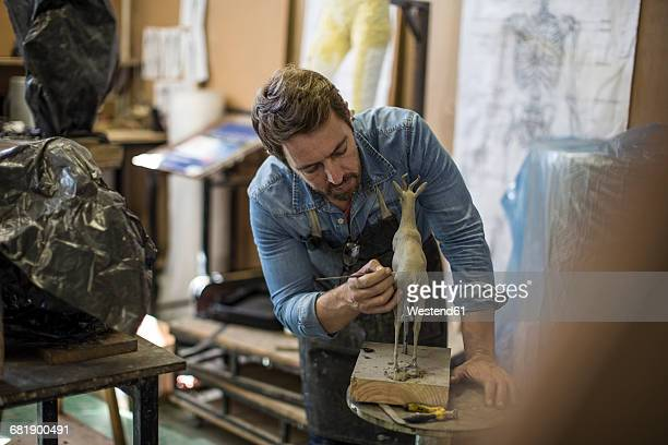 sculptor working in studio on animal figurine - sculptor stock pictures, royalty-free photos & images