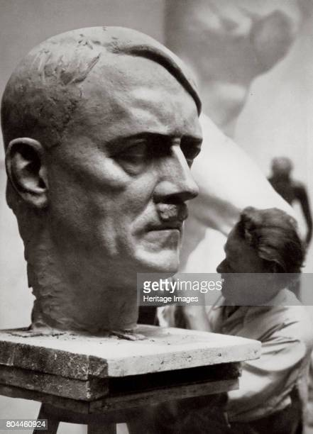A sculptor working on a large portrait bust of Adolf Hitler Germany 1936 Artistic creative work expressive of the new national spirit From Germany...