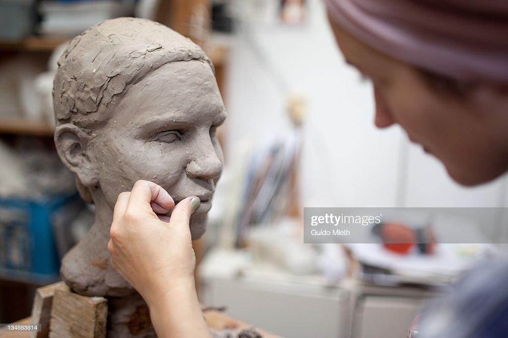 Sculptor working on head sculpture : Stock Photo
