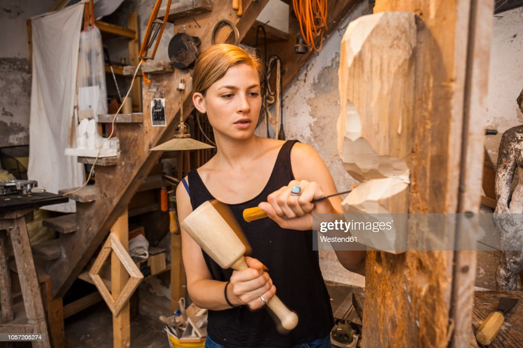 Sculptress carving wooden figure : Stock Photo