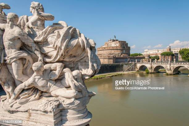 sculptural group on vittorio emanuele ii bridge, on the background ponte sant'angelo and castel sant'angelo - image stock pictures, royalty-free photos & images