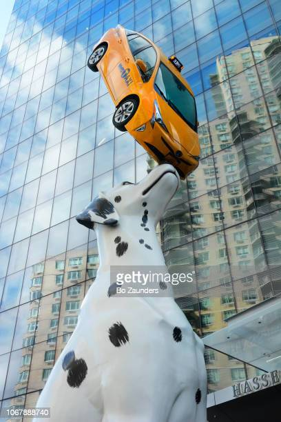 Sculpture by Donals Lipsky of a  Dalmation dog balancing a real taxi, outside NYU Langone Hospital at 34th street and 1st avenue in NYC.  a real taxi,