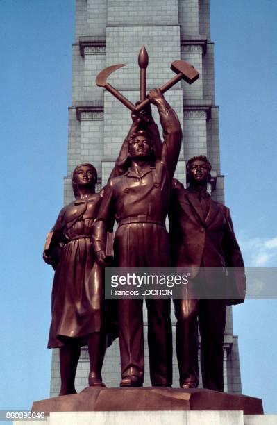 Sculpture en bronze devant la tour du Juche représentant un ouvrier un paysan et un intellectuel en juillet 1987 à Pyongyang Corée du Nord