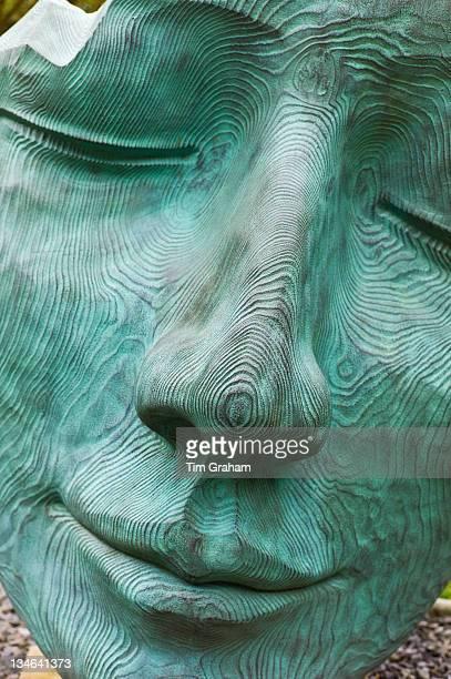 Sculpture Fallen Deodar by Jilly Sutton monumental death mask verdigris bronze on timber at Broomhill Sculpture Gardens Devon UK