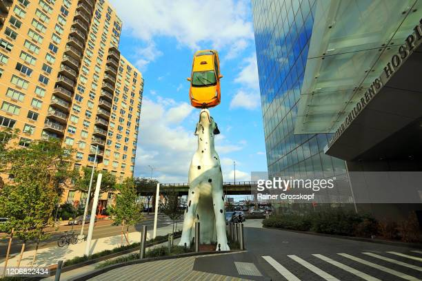 sculpture of a dalmatian puppy balancing a real new york city yellow cab on its nose. - rainer grosskopf stock-fotos und bilder