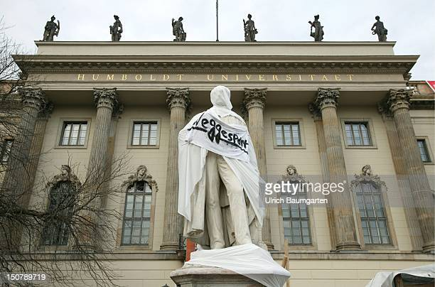 Sculpture of Alexander von Humboldt in the backround the Humboldt University Berlin