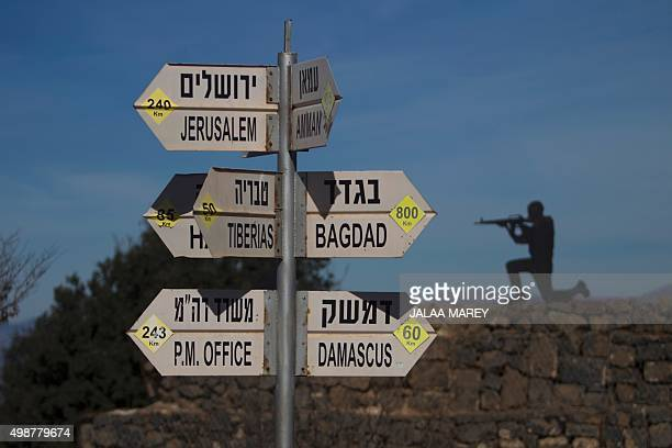 A sculpture of an Israeli soldier standing guard is seen on November 25 2015 next to a sign for tourists showing the distance to Damascus and Baghdad...