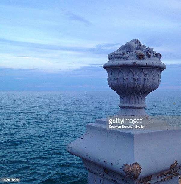 Sculpture Of Cup On Pedestal, Sea In Background