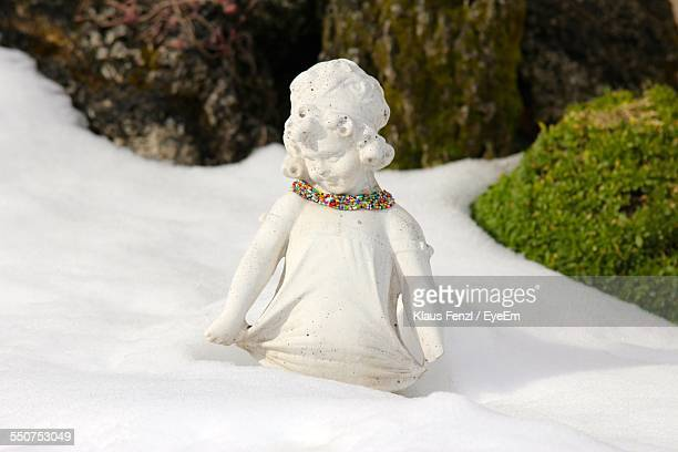 Sculpture Of Girl Adorned With Colorful Beads On Snowy Field