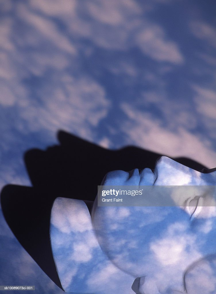 Sculpture of head with projected clouds, studio shot : Stockfoto
