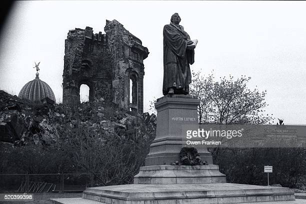 sculpture of martin luther stands besides ruins of a building - bombardamento di dresda ii guerra mondiale foto e immagini stock