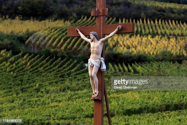A sculptured stone crucifix stands in front of rows of vines as autumn colors mark a change in seasons on October 10 2019 in the village of...