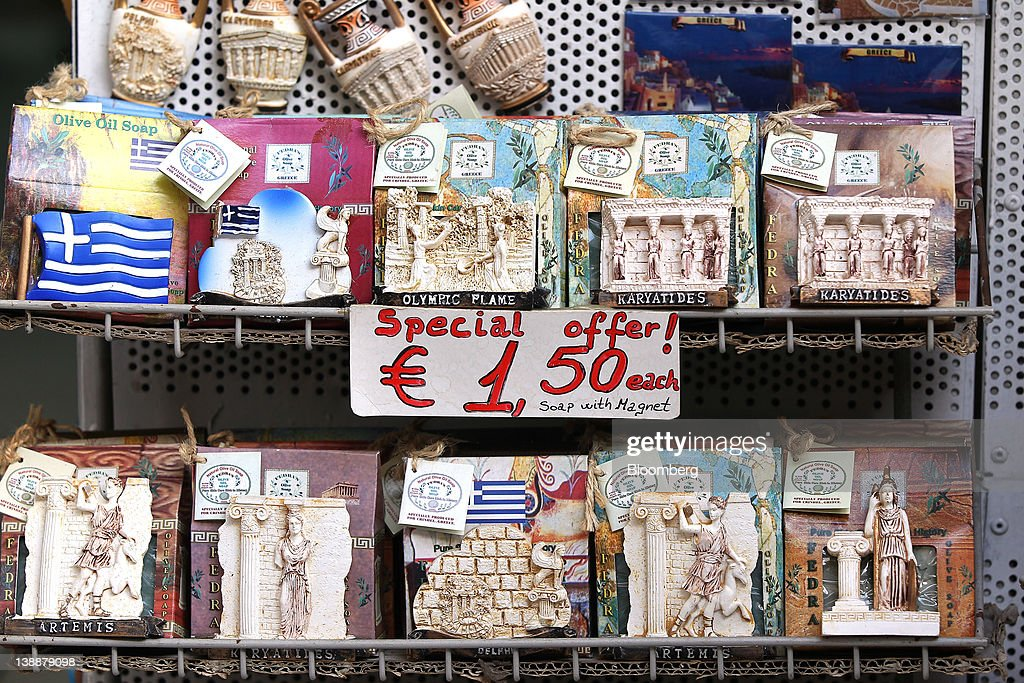 Sculptures of Greek gods sit for sale alongside a sign that reads 'special offer' at a gift store in Athens, Greece, on Sunday, Feb. 12, 2012. Greek Prime Minister Lucas Papademos won parliamentary approval for austerity measures to secure an international bailout after rioters protesting the measures battled police and set fire to buildings in downtown Athens. Photographer: Simon Dawson/Bloomberg via Getty Images