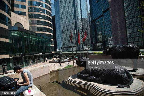 Sculptures of water buffalo stand in a plaza at Exchange Square in Hong Kong China on Tuesday April 14 2015 Chinese stocks trading in Hong Kong fell...