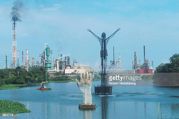 Sculptures protrude from the Magdalena River August 21 2000 in front of Colombia's largest petroleum refinery which supplies 70% of the nation's...