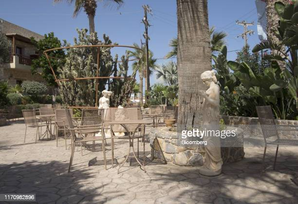 Sculptures stand alongside empty chairs on the front terrace of Cactus hotel, in Hersonissos, on the island of Crete, in Greece, on Tuesday, Sept....