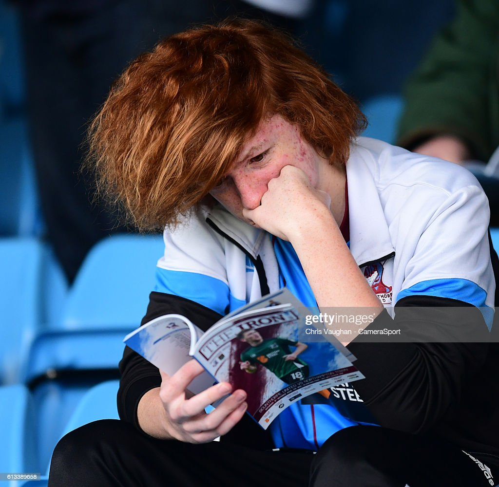A Scunthorpe United fan reads the match day program before the Sky Bet League One match between Scunthorpe United and Northampton Town at Glanford Park on October 8, 2016 in Scunthorpe, England.