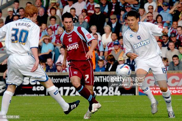 Scunthorpe United's Matthew Sparrow passes through Brighton Hove Albion's Alex Revell and Tommy Fraser
