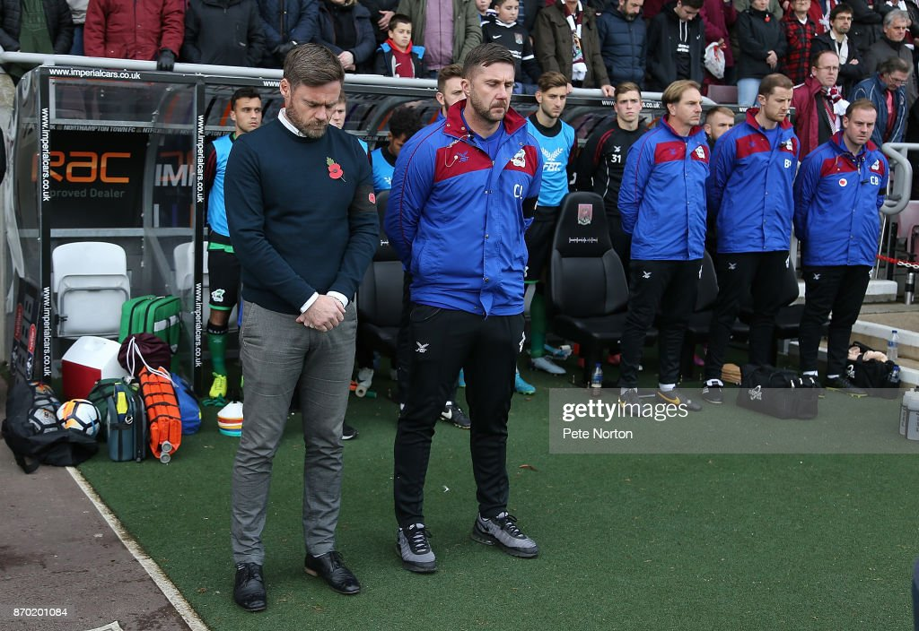 Scunthorpre United manager Graham Alexander along with his assistant Chris Lucketti and substitutes observe a remembrance minutes silence prior to The Emirates FA Cup First Round match between Northampton Town and Scunthorpe United at Sixfields on November 4, 2017 in Northampton, England.
