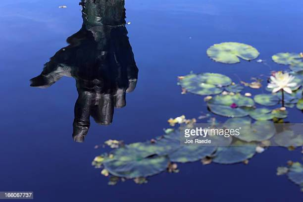 A scuplture by artist Kenneth Treister is reflected in water at the Holocaust Memorial during Yom HaShoahHolocaust Remembrance Day on April 8 2013 in...