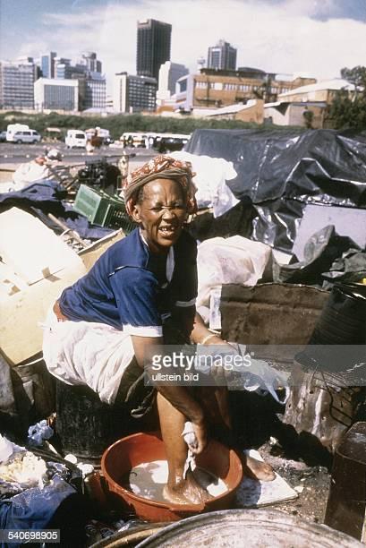 Die Obdachlose Victoria Mogobe wäscht sich in einem Wassereimer die Füße Eine Müllhalde in Johannesburg ist ihr Arbeitsplatz und Wohnort Hier sucht...