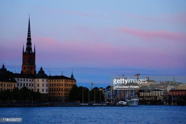 södermalm and riddarholmen island at dusk, stockholm, sweden - riddarholmkirche stock-fotos und bilder