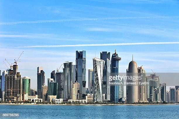 sea against doha tower and modern buildings in city - doha stock pictures, royalty-free photos & images