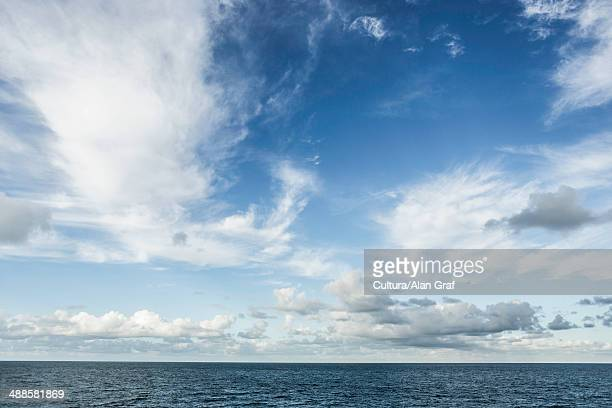 sea and blue sky with clouds - atmospheric mood stock pictures, royalty-free photos & images