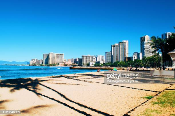 sea and buildings against clear blue sky - 沿岸 ストックフォトと画像