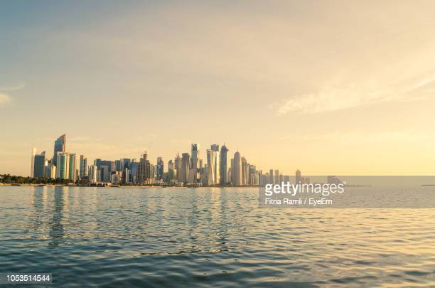 sea and buildings against sky during sunset - doha photos et images de collection