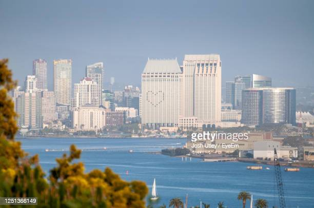 sea and buildings in city against sky - josh utley stock pictures, royalty-free photos & images