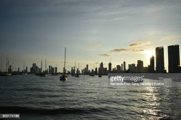 Sea And Cityscape Against Sky During Sunset