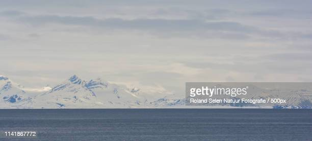 Sea and snowcapped mountains with cloudy sky in background