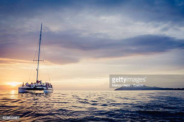 sea at sunset - catamaran stock photos and pictures