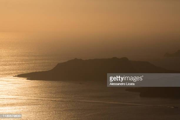 sea ​​at sunset with island and ship - turista stockfoto's en -beelden