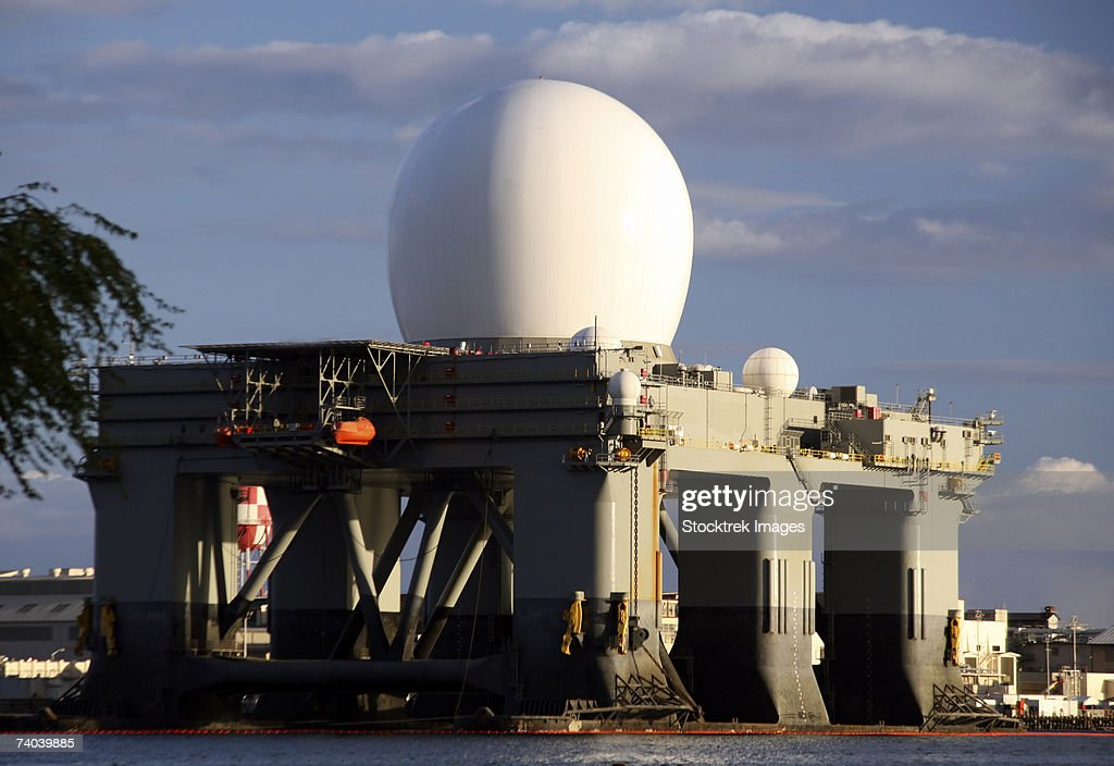 Sea Based X-band Radar dome modeled by the setting sun at Pearl Harbor naval shipyard where this component of the Ballistic Missile Defense System is undergoing maintenance and repair. : Stock Photo