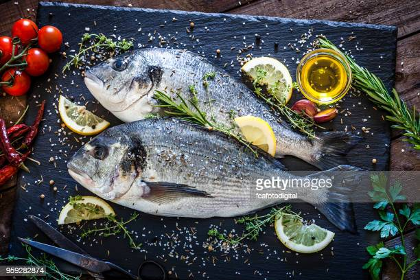 sea bream and ingredients for cooking and seasoning - seafood stock pictures, royalty-free photos & images