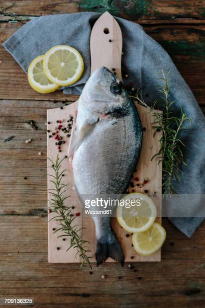 Sea Bream on a wooden board with pepper and rosemary