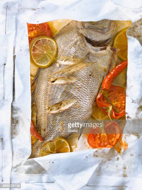 Sea bream with lime,tomatoes and pepper cooked in wax paper
