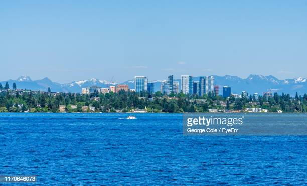 sea by buildings against blue sky - bellevue skyline stock pictures, royalty-free photos & images