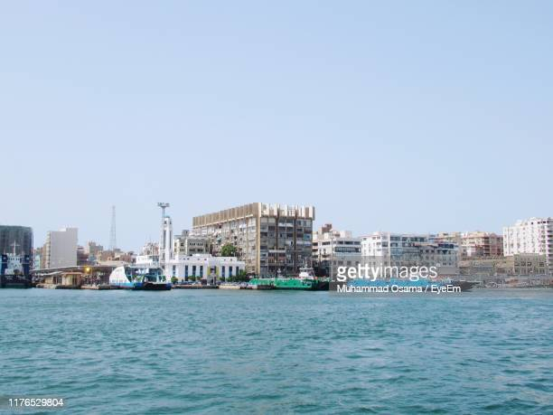 sea by buildings against clear sky - port said stock pictures, royalty-free photos & images