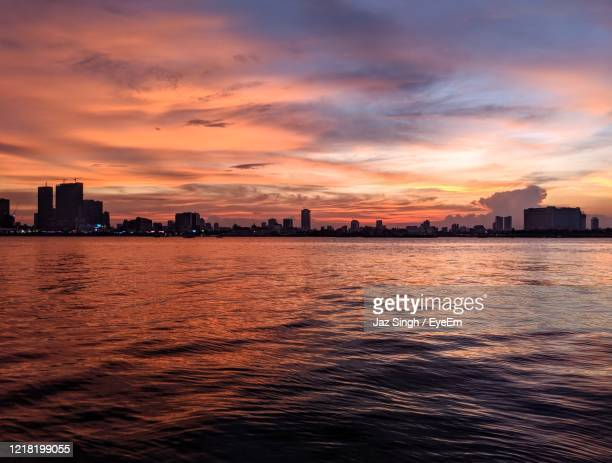 sea by buildings against sky during sunset - night life in cambodian capital phnom penh ストックフォトと画像