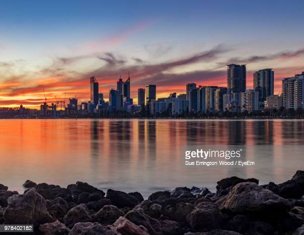 sea by buildings against sky during sunset - perth stock pictures, royalty-free photos & images