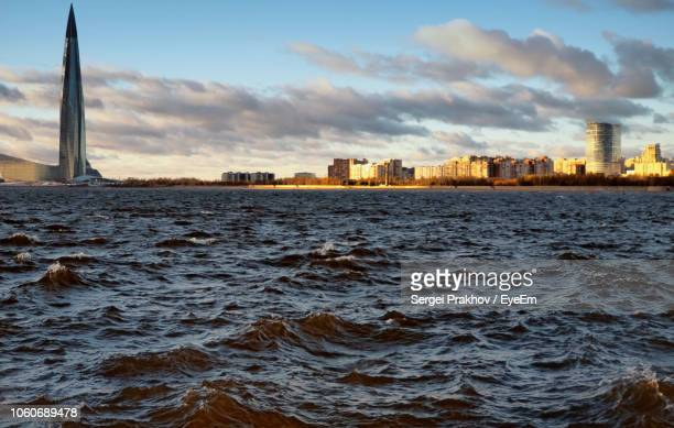 sea by buildings against sky in city - sergei stock pictures, royalty-free photos & images