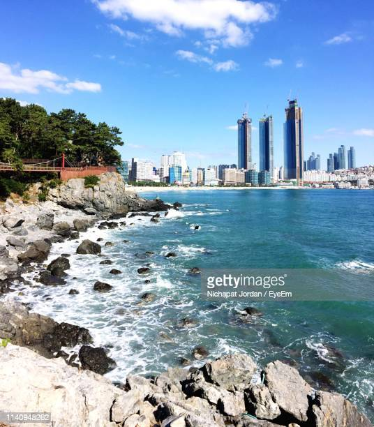 sea by buildings in city against sky - busan stock pictures, royalty-free photos & images