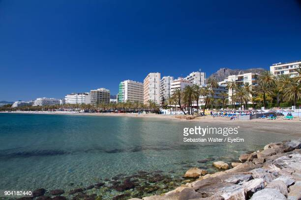 sea by city against clear blue sky - marbella stock pictures, royalty-free photos & images